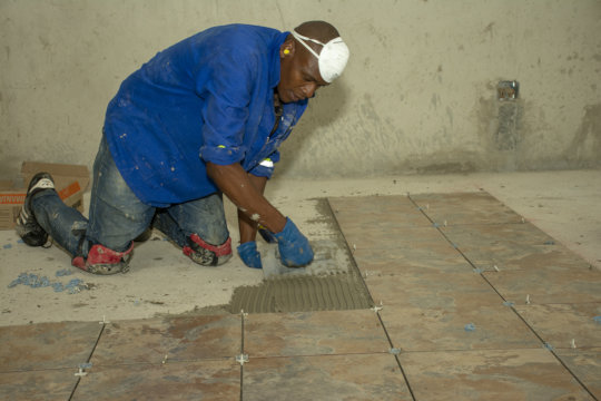 A local man doing tiling at the guest house