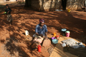 Gogo cracking marula nuts in the traditional way