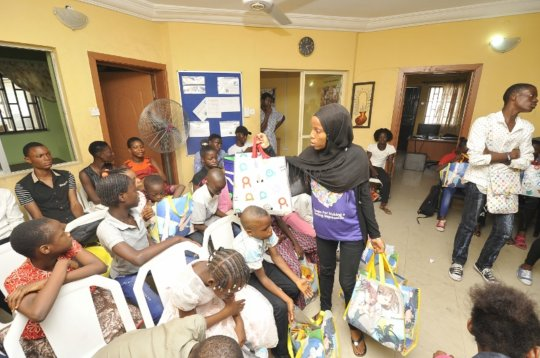 Nishola distributes party packs to the children