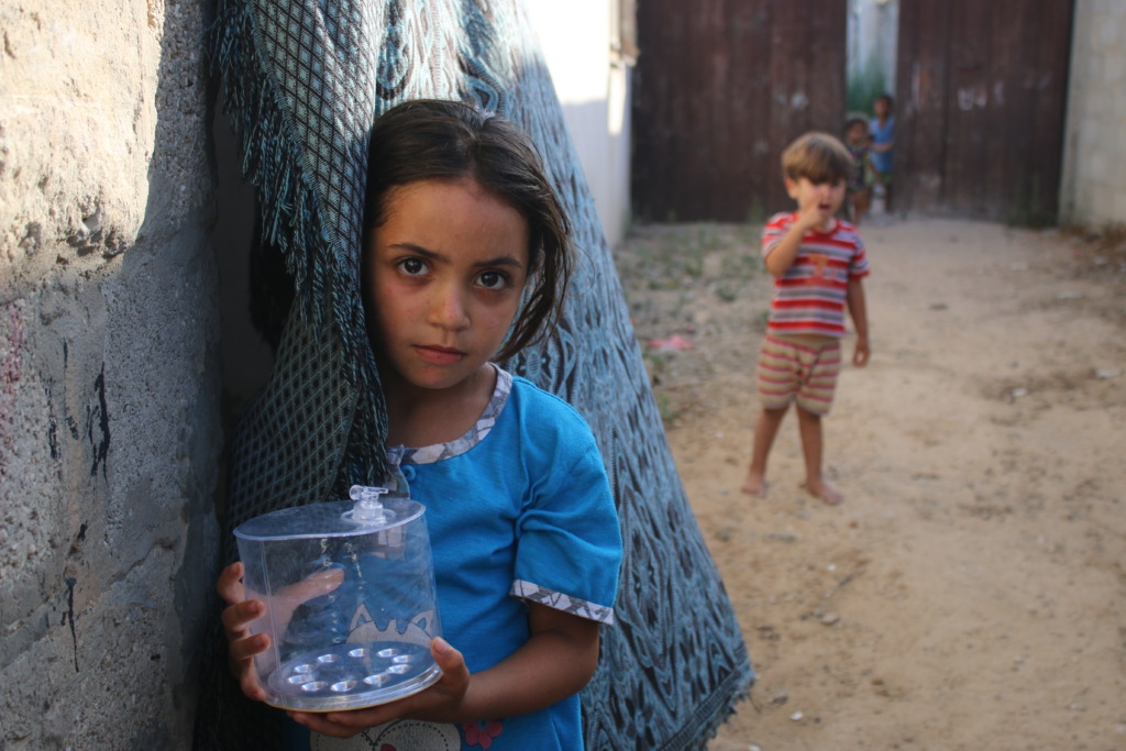 A girl in Gaza poses with her Luci light
