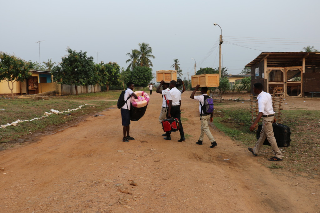 Students with their items walking to their hostels