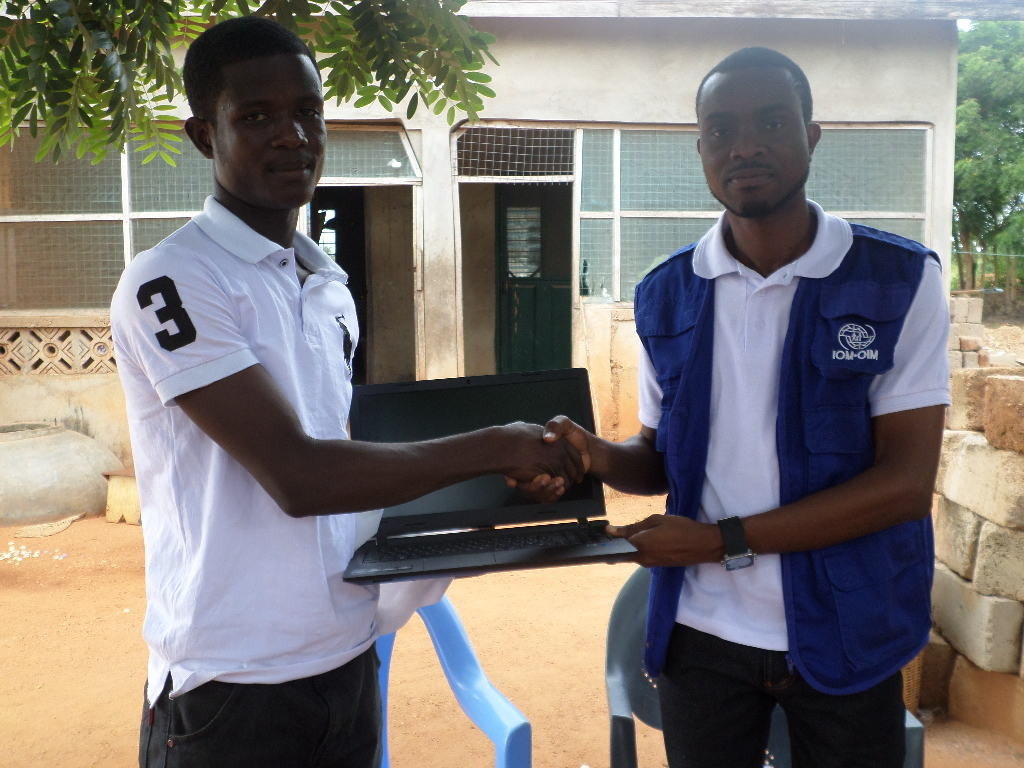 James receiving a laptop from IOM staff