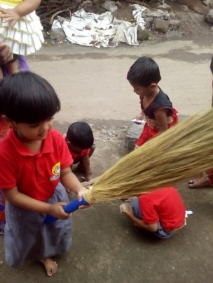 A child using a broomstick to clean the premise