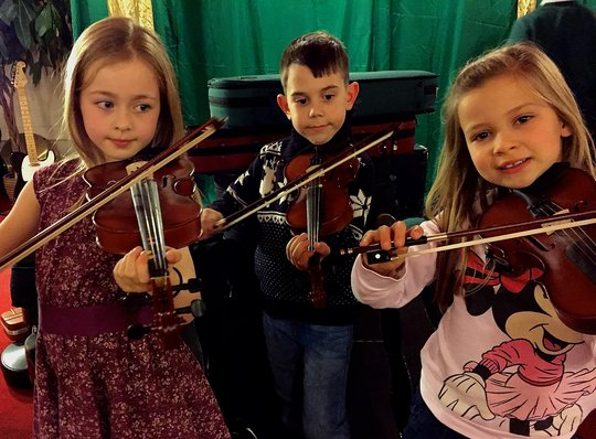 Young people playing the donated violins