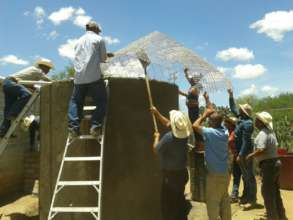 Local community members placing the cistern roof