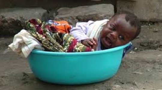 Kayayoo Baby in a Head Pan while Mother Works