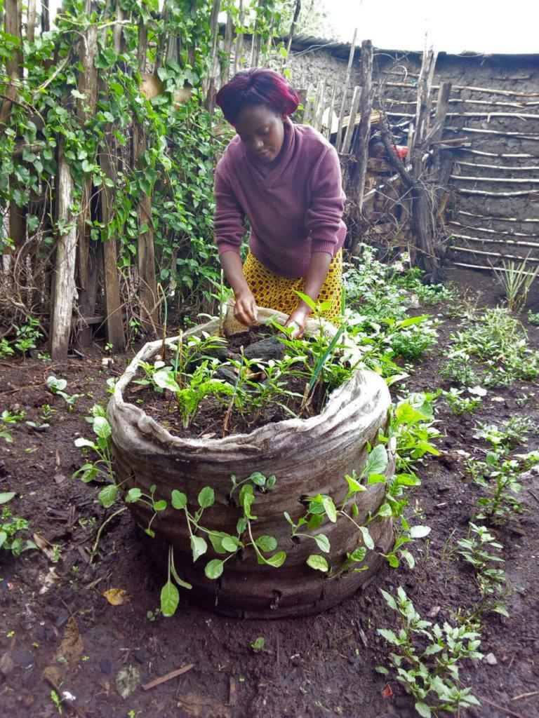 Lucy weeding her vertical bag garden