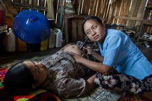 Birth attendant preforms monthly checkup
