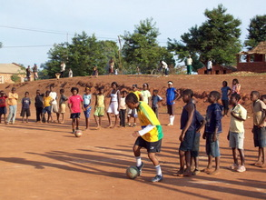 Sarita, in yellow, shows young players how to control the ball w