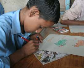 Rural child painting in his drawing book