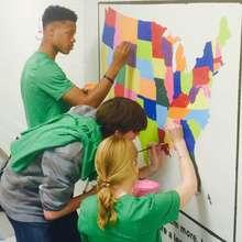 Starbucks volunteers rehabilitate an old mural.