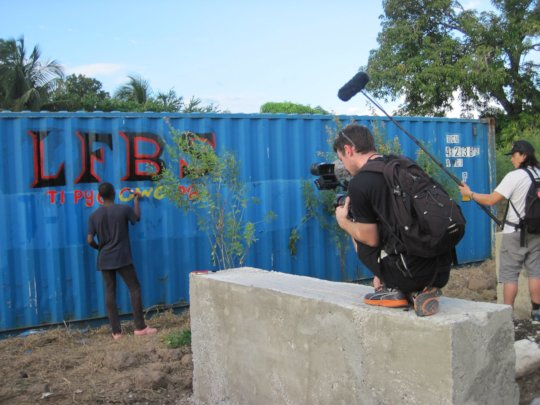 Youth painting storage container on LFBS land