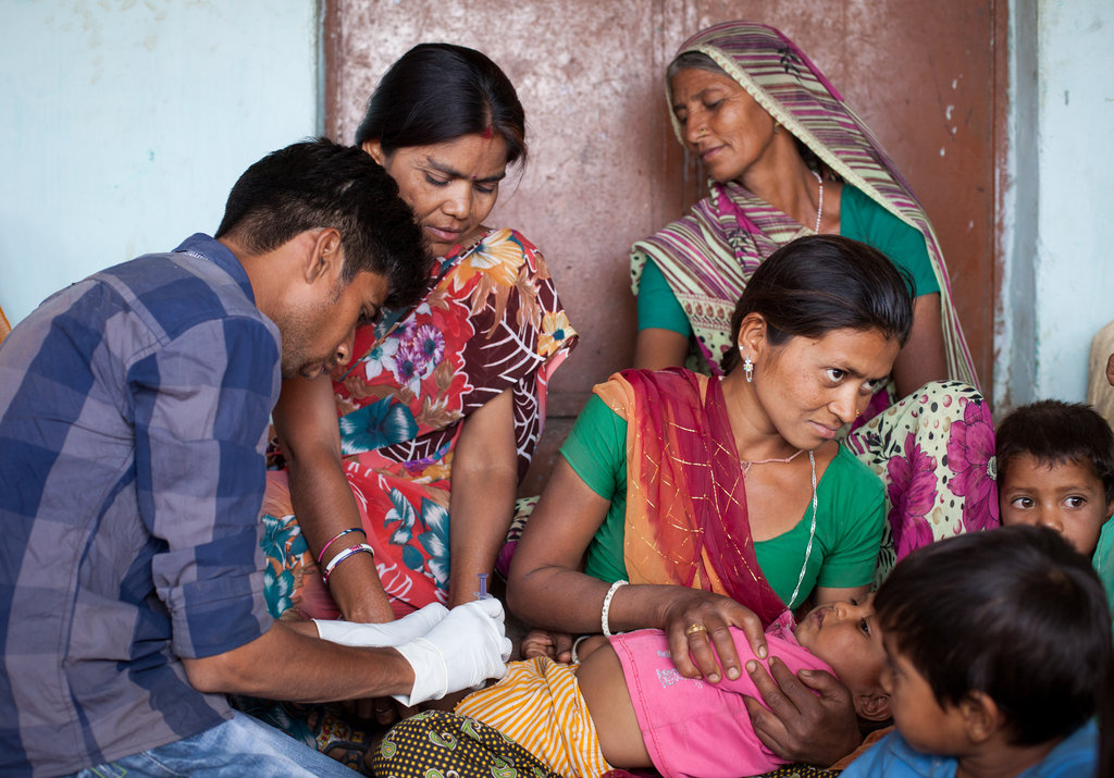 A health worker gives a child an immunization.