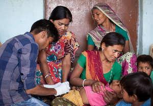 A health worker gives a child an immunization.