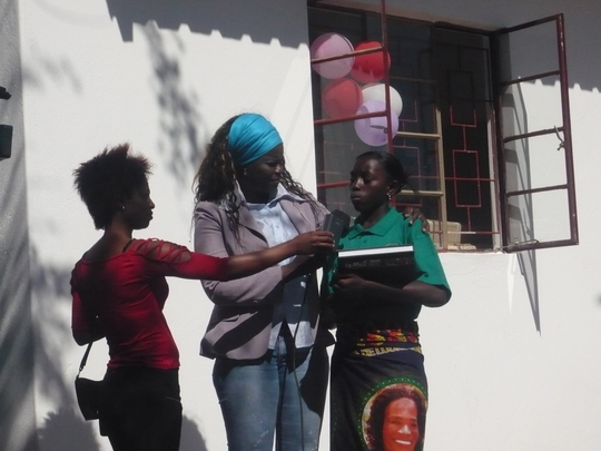 Milca, last year's top student, reads a poem with media present.