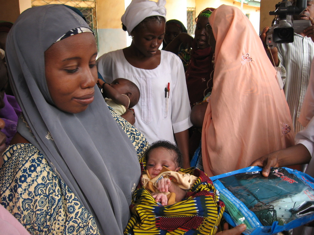 A nursing mother receives insecticide treated net for her baby