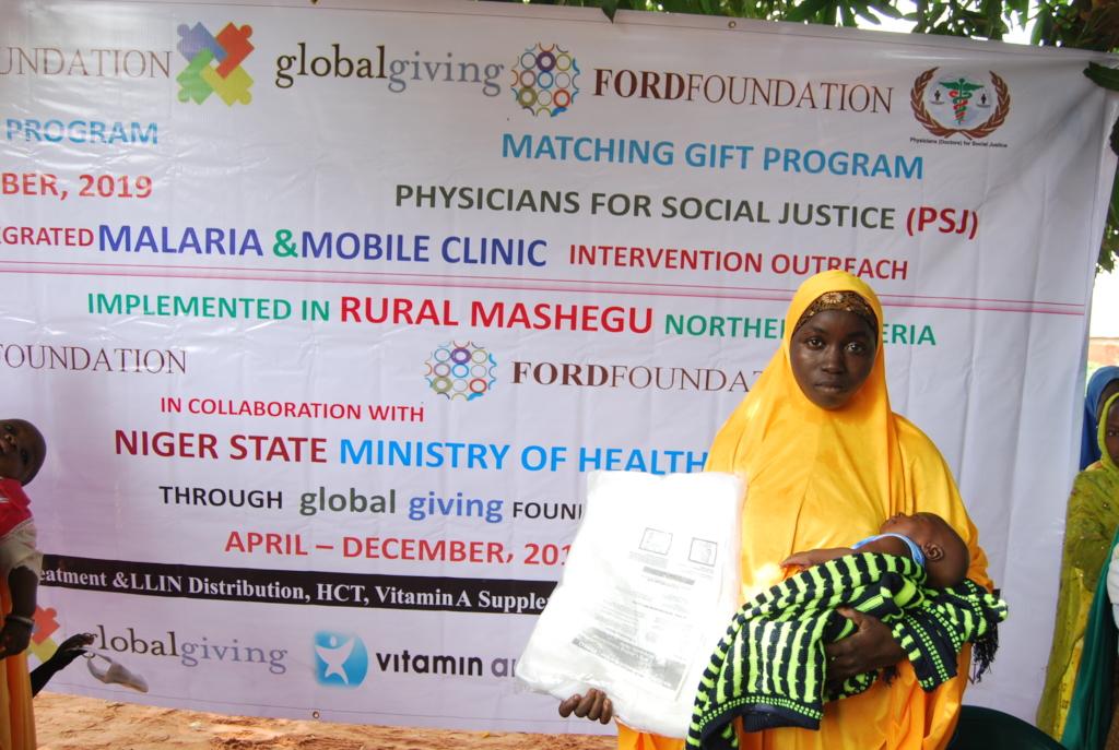 Nursing mother shows off her LLIN at Adogo village