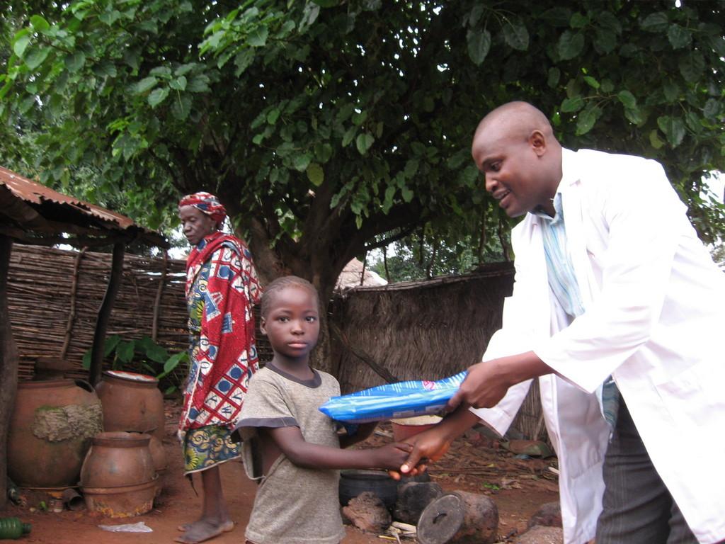 PSJ volunteer giving ITN to an OVC