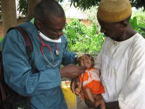PSJ physician attending to an infant in rural Mash