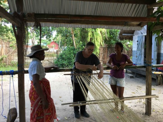 Threading the peddle loom with team