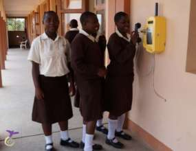 Girls using the school phone to call the guardians