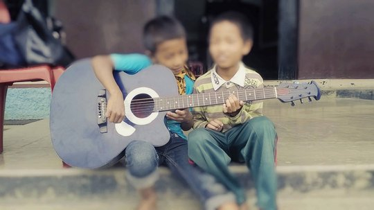 Children practicing guitar lessons