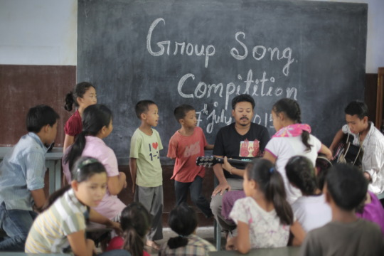 Akhu teaching music to the children