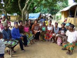 Sahadatu (center) meets with families in Kenema.