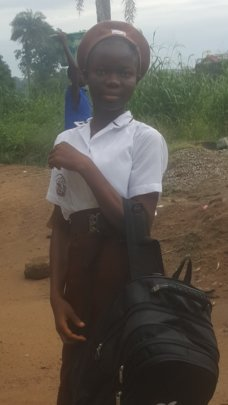 Zainab with her new uniform and school supplies.