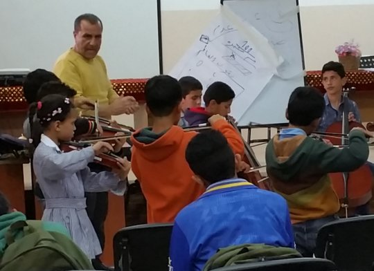 Maestro Mohammad Fadel instructs Al Aqaba students