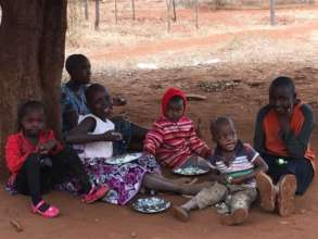 Kids eat a nutritious meal under the shade tree.