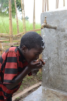 A boy washes her face with a CLEAN water supply