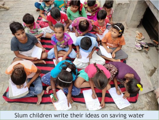 Slum children engrossed in writing their ideas