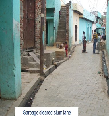 Slum lane looks neat after garbage is cleaned up