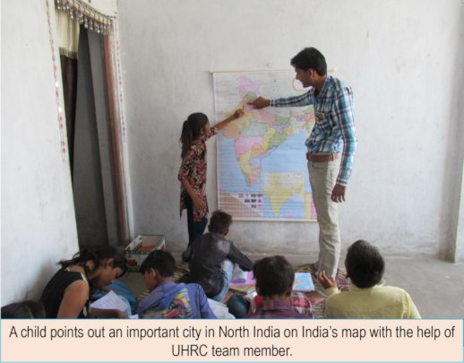 A girl points out a city on India's map