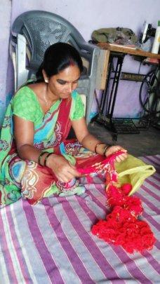 Woman weaving garment in slum house