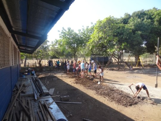Students helping dig the trench at our school