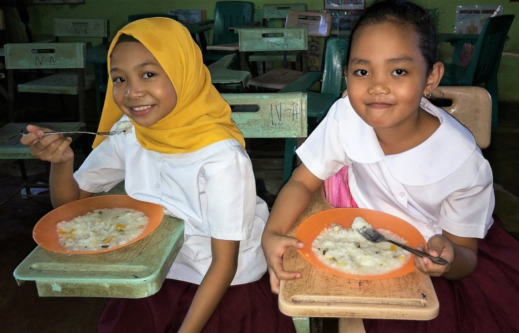 Muslim and Christian children receive school lunch