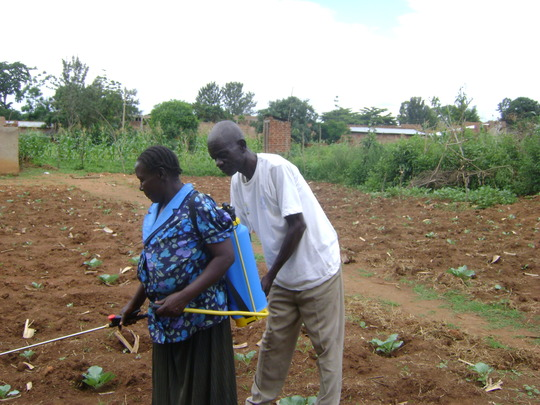 OFFICER TRAINS A WIDOW TO OPERATE A SPRAY PUMP