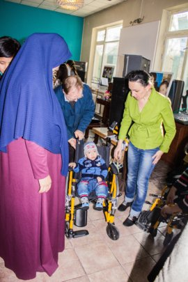 A disabled child getting a wheelchair in the cafe