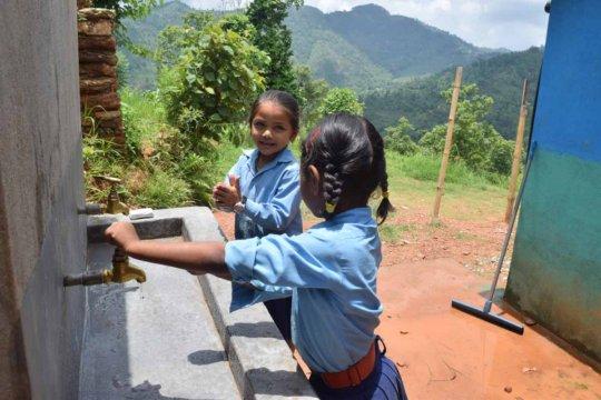 Anjuta and Aashika wash their hands