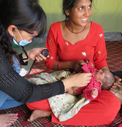 Kapana holds her daughter, Kumari, for a check-up