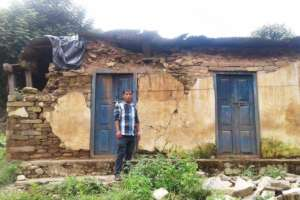 Shambu stands in front of his home today