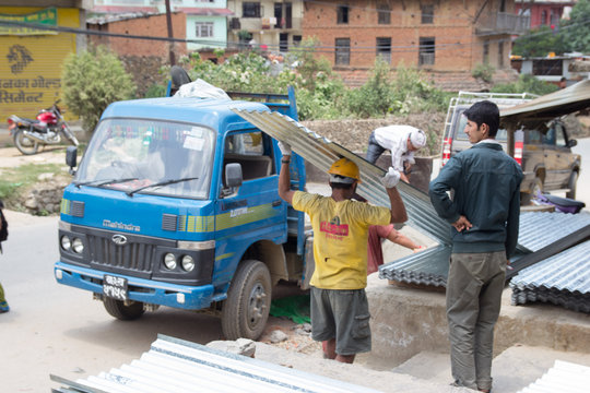 Metal sheet roofing being delivered to families.