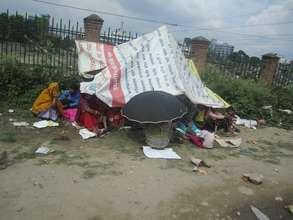 Earthquake survivors huddle under a tarp.