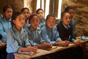 Students attending class in a school built by HHC