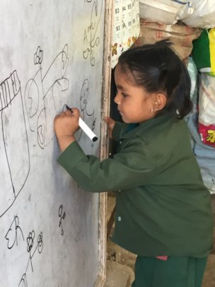 Young girl writes on ETC-provided white board