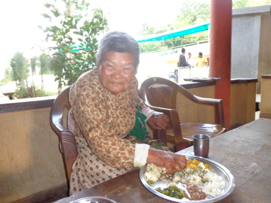 A old woman having  her meal.