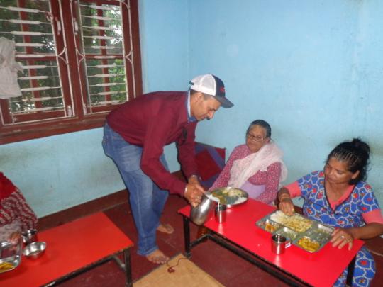 Chairman of CDC Nepal distributin milk to elderly