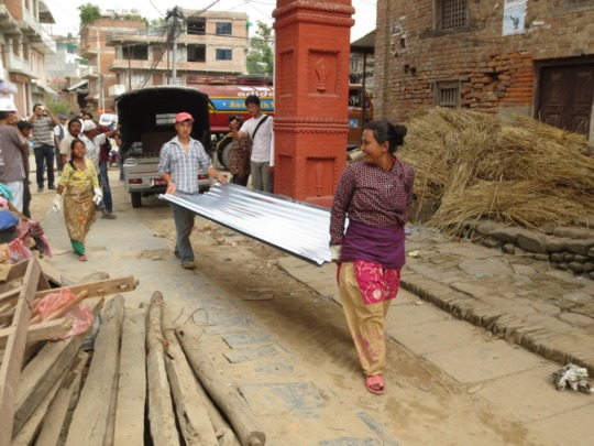 Unloading iron roofing material for shelters